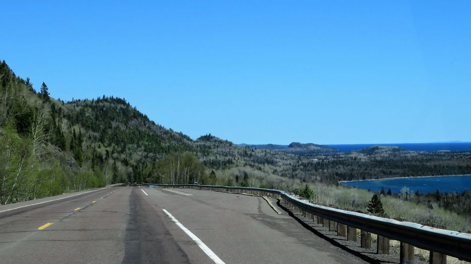 HWY 61 Summer Road Tripping Beauty In Nature Clear Sky Copy Space Crash Barrier Day Diminishing Perspective Direction Dividing Line Marking Mountain Nature No People Outdoors Plant Road Road Marking Sign Sky Symbol The Way Forward Tranquil Scene Tranquility Transportation Tree
