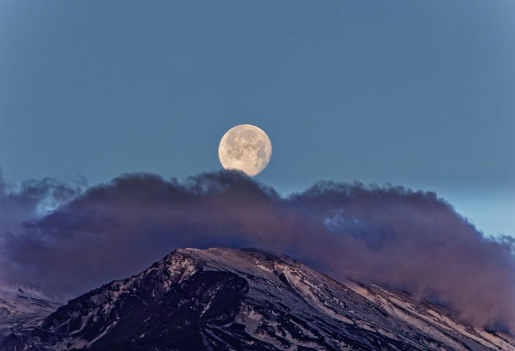 Low angle view of the snowy peak of etna volcano with moon setting