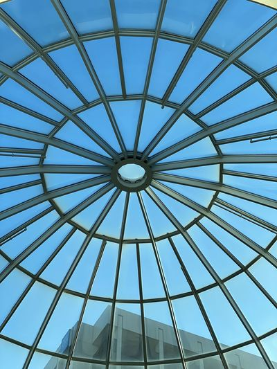 Low angle view of skylight in building against sky