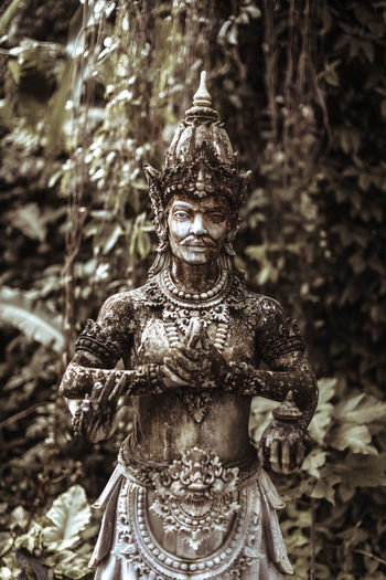 Balinese statue stone figure of the god. water palace of tirta gangga in east bali, indonesia.