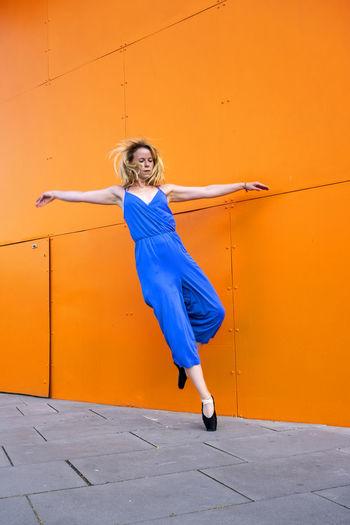 Full length of woman dancing against orange wall