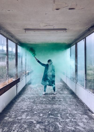 Woman With Green Smoke Flare In Corridor