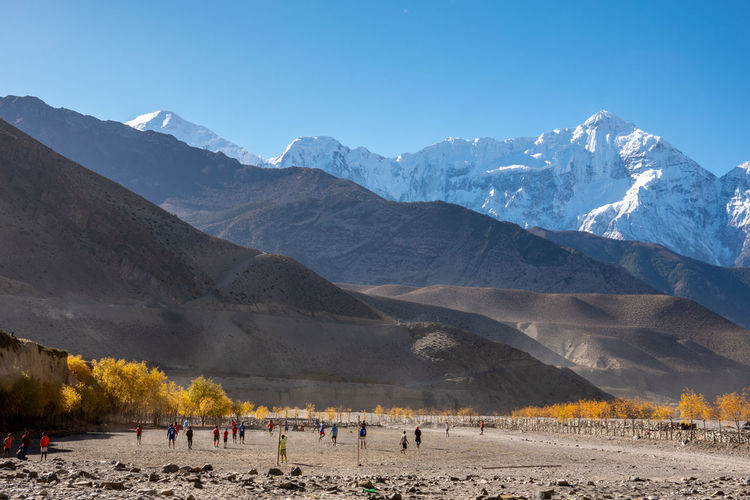 People standing against snowcapped mountain during sunny day