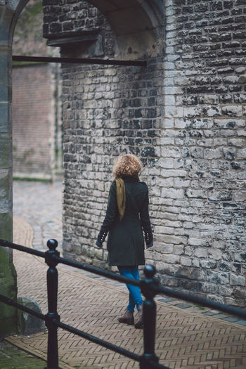 Rear View Of Woman Wearing Warm Clothing While Walking On Footpath In City