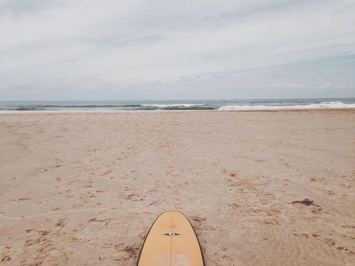 Surfboard on beach against sky