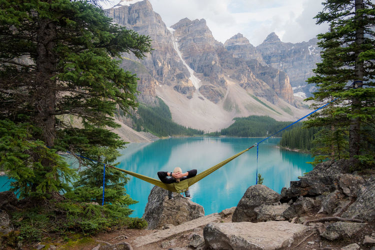 High angle rear view of man resting on hammock in front of lake in mountainous landscape