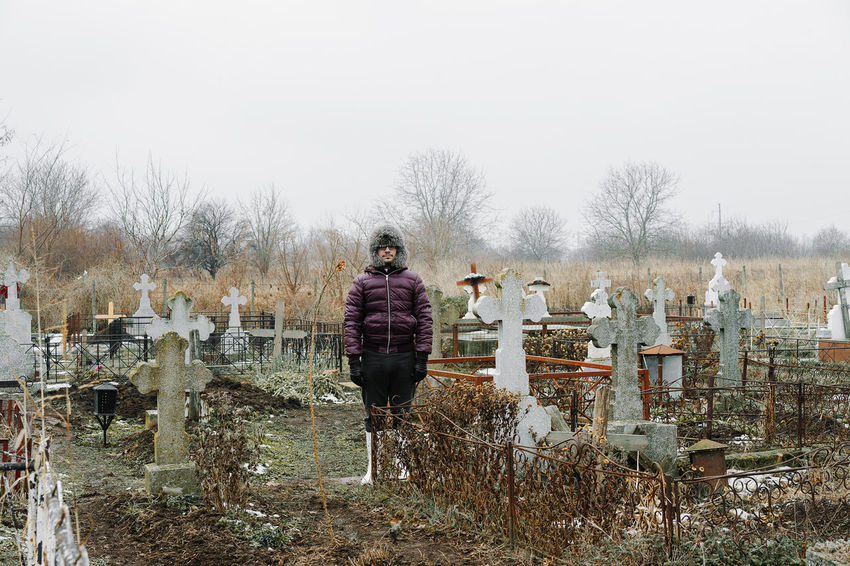 Cemetery Winter Cold Temperature One Person One Man Only Men Warm Clothing Graveyard Gravestone Sky Cold Fur Hat Winter Coat Place Of Burial Cross Fence Bare Tree