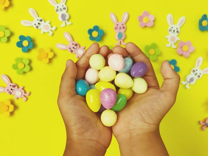 Cropped Hands Of Child Holding Easter Eggs Over Yellow Background