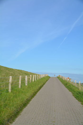 Road By Grassy Field Against Sky