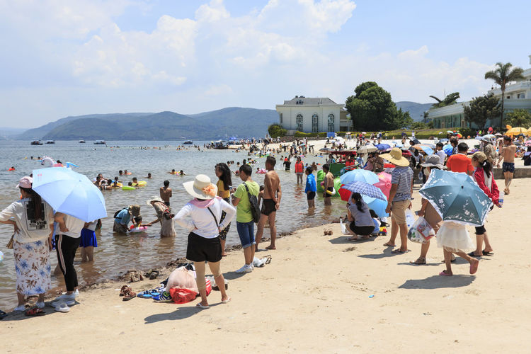 Yuxi, China - July 29, 2017: Chinese tourists on a beach of the Fuxian Lake in Yunnan, the thid deepest lake in China. It is located halfwy between the capital Kunming and Yuxi. Erhai Lake,Dali Fuxian Lake Swimming Tourist Beach Chinese Shore Umbrella Yunnan ,China Yuxi,