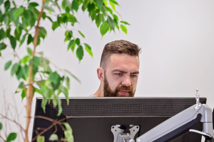 Man looking at computer while sitting in office