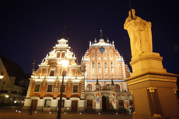Low Angle View Of Statue And Illuminated Buildings Against Sky At Night