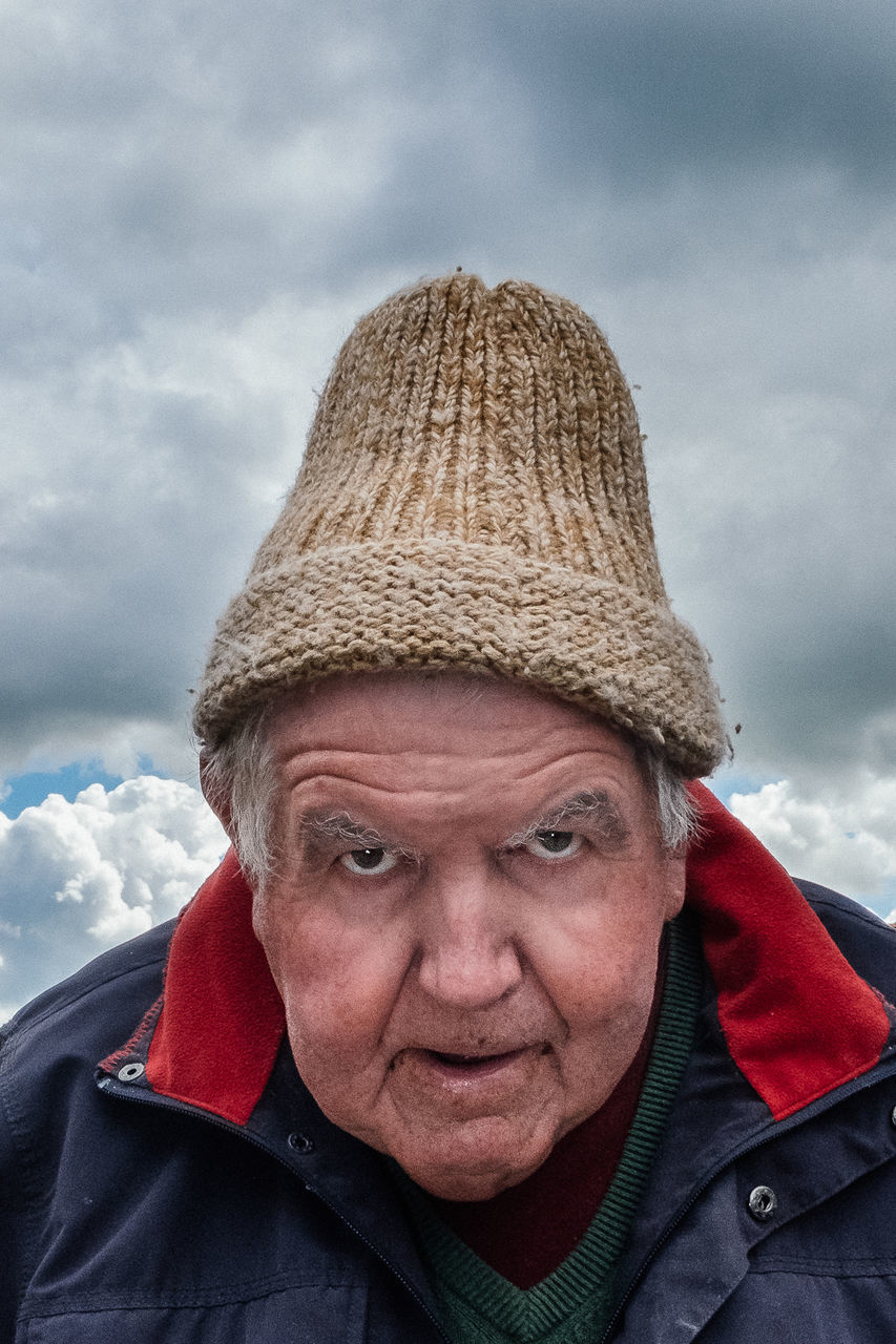 PORTRAIT OF MATURE MAN WEARING HAT AGAINST CLOUDS