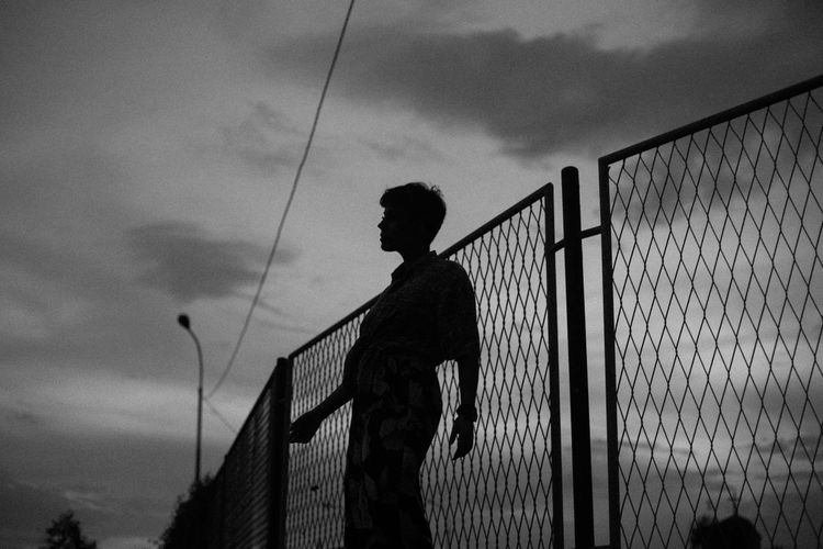 Silhouette man standing by fence against sky