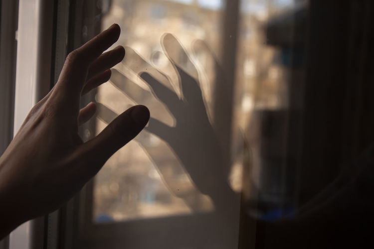 Cropped hand of person touching glass window