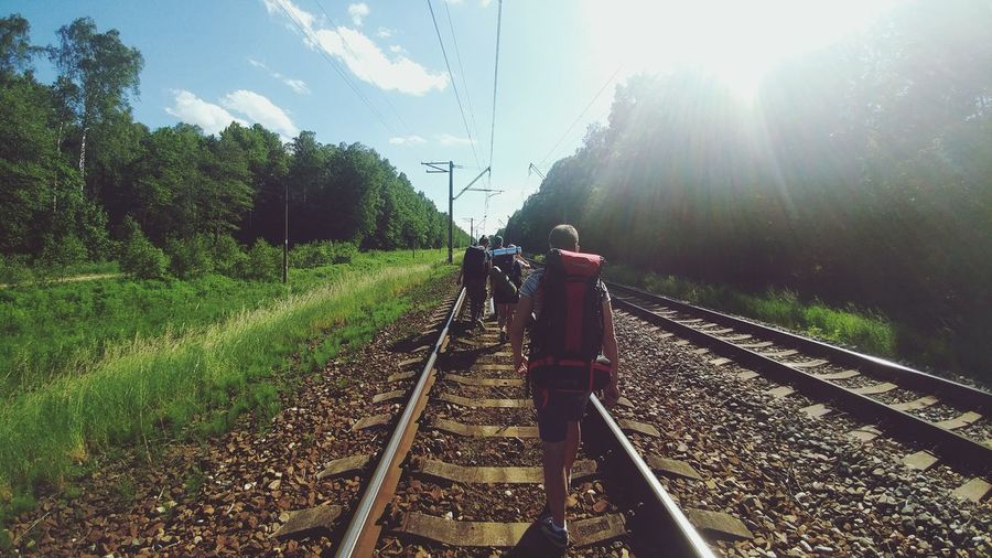 Rear View Of Hikers With Backpacks Walking On Railroad Track Amidst Trees Against Sky