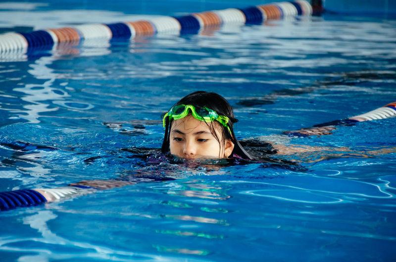 Closeup portrait of cute little peruvian girl swimming in the pool, happy child having fun in water