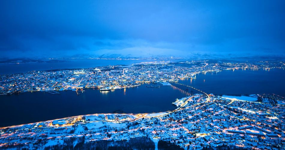 High angle view of illuminated city by sea against blue sky