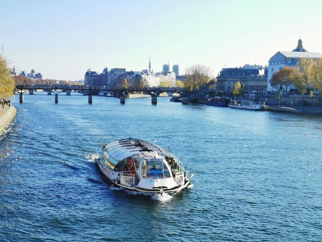 view of a cruise boat on Seine River in Paris city center with Notre-Dame Cathedral on background City Cityscape Cruise Cathedral Notre Dame De Paris Landscape Landmark Blue Urban Backgrounds Travel Destinations Famous Place Seine Autumn Season  Colorful Nautical Vessel City Water Ferris Wheel Cityscape Skyscraper Urban Skyline High Angle View Tree Architecture Boat Sailing Boat Moving Ferry