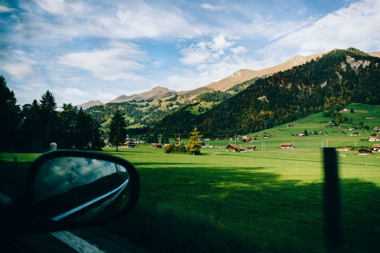 Car on field by mountains against sky
