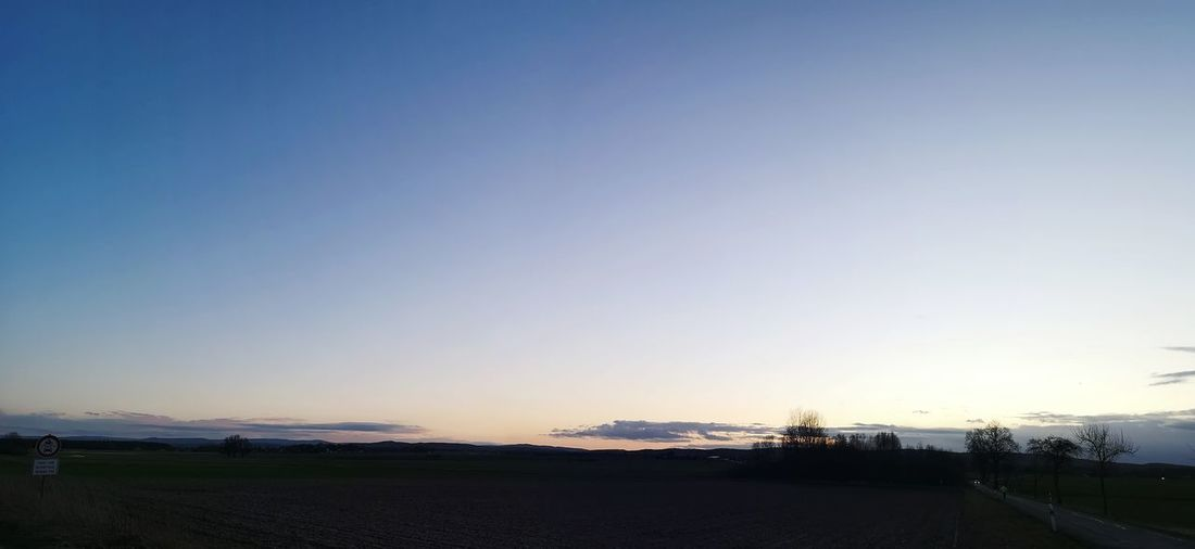 Scenic view of road against clear sky during sunset