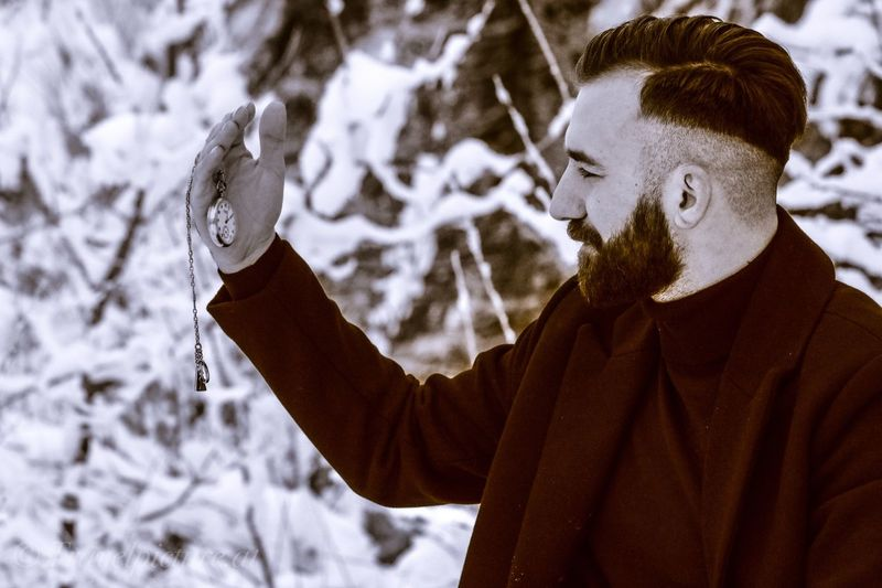Young man holding pocket watch during winter