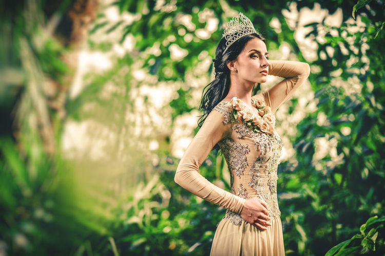 Gorgeous lady in evening dress and with tiara on a head posing in a forest Crown Elégance Fashion Princess Romantic Slim Summertime Tiara Trees Well-dressed Woman Beautiful Woman Diadem Evening Dress Female Forest Garden Glamour Gorgeous Gown Lush Foliage One Person Outdoors Tropical Garden Young Adult