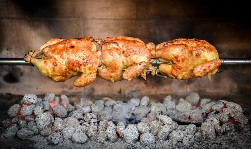 Close-up of chicken with rotisserie on barbecue