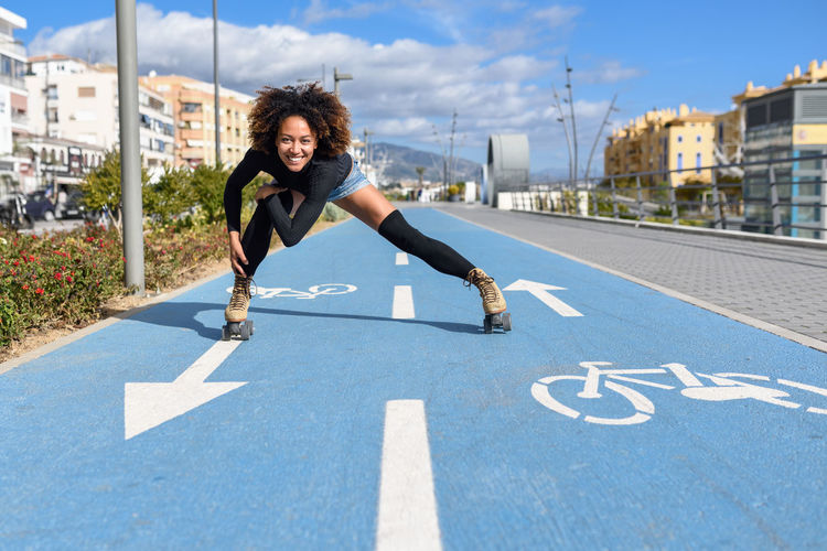 Portrait Of Woman Roller Skating On Bicycle Lane In City