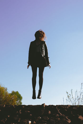 Low angle view of woman levitating against clear sky