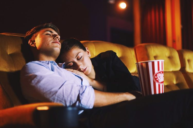Couple relaxing with popcorn in movie theater