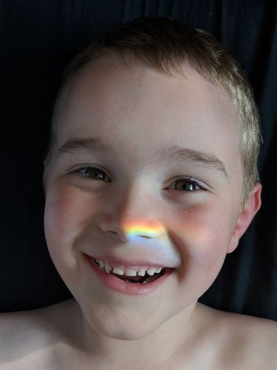Close-up portrait of cheerful boy with spectrum on his nose
