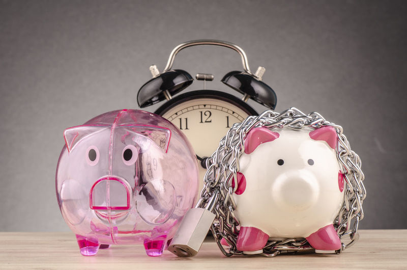 piggy bank surrounded by chains and padlock on wooden desk Indoors  Still Life Pink Color Piggy Bank Studio Shot Investment No People Savings Animal Representation Close-up Representation Art And Craft Table Animal Wealth Finance Toy Mammal Alarm Clock Clock Luxury