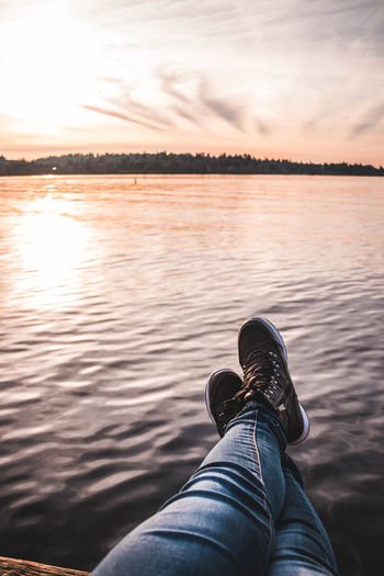 Low section of person relaxing against lake during sunset