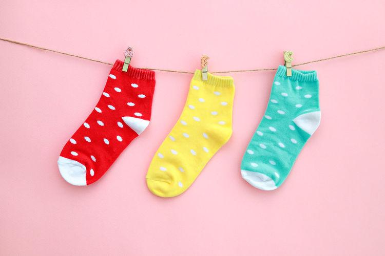 Multi Colored Socks Hanging On Clothesline Over Pink Background