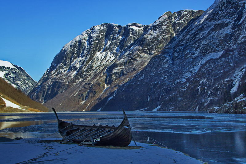 Boat Moored At Lakeshore Against Mountain