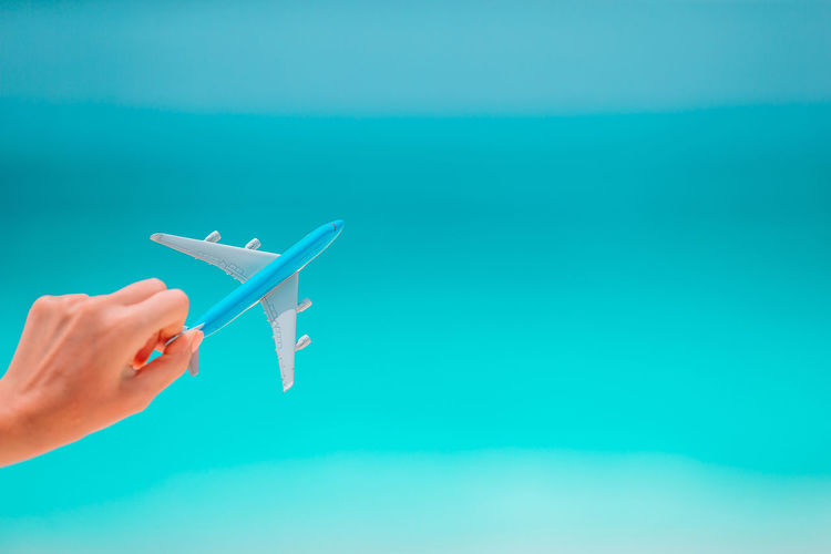 Cropped image of person holding airplane in swimming pool