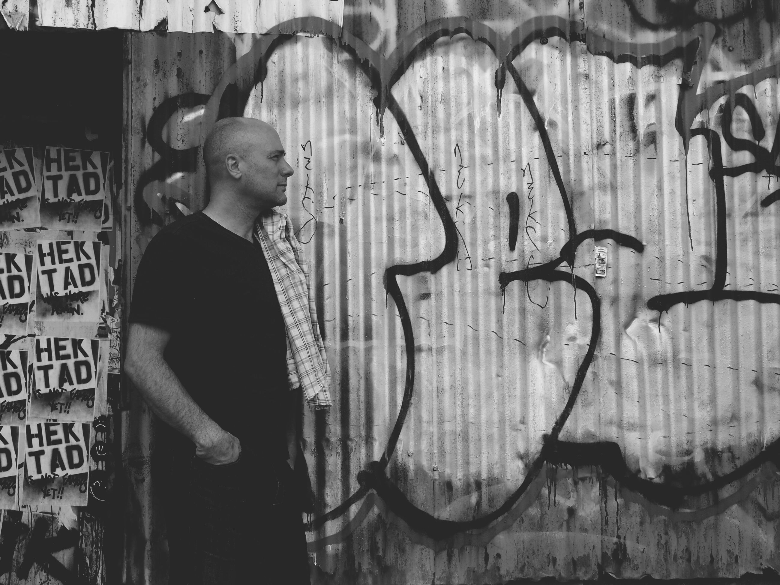 graffiti, lifestyles, text, wall - building feature, leisure activity, communication, casual clothing, western script, built structure, standing, architecture, full length, building exterior, men, art, young adult, person, front view