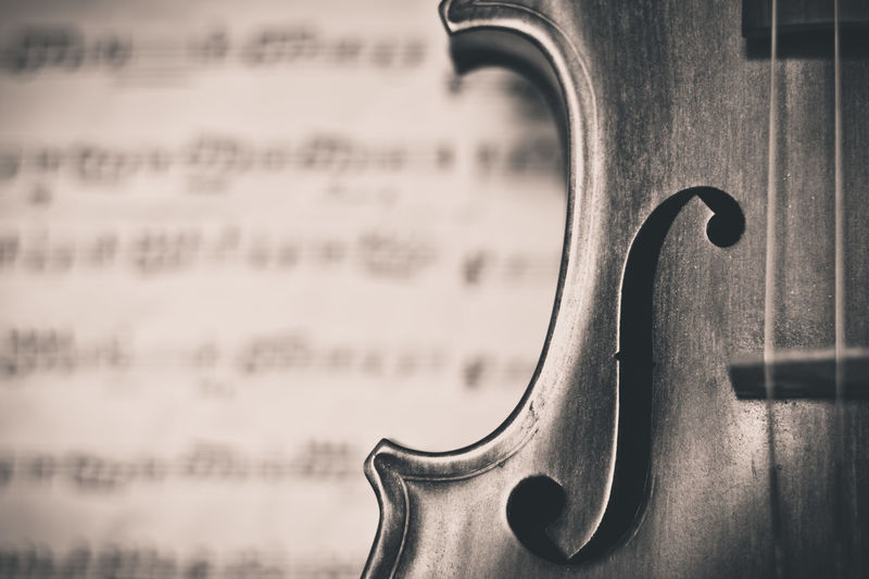 Cropped Image Of Cello Against Sheet Music