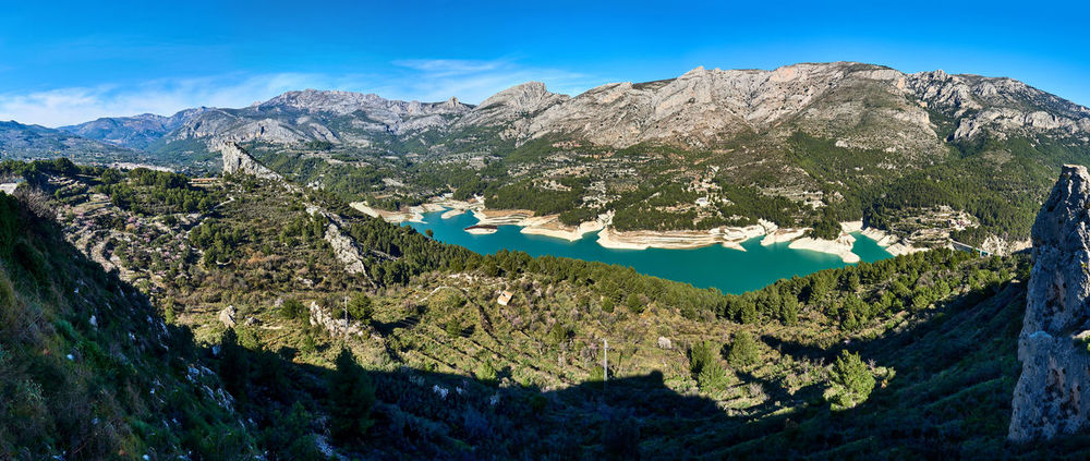 Panoramic view of Guadalest Reservoir. Beautiful view of the valley with a dam and reservoir. Costa Blanca, Province of Alicante. Spain Aerial View Alicante Province Spain Artificial Lake Beauty In Nature Bright Colors Costa Blanca Green Water Guadalest Lake Landmark Landscape Mountains Nature Panorama Panoramic Picturesque Scenery Reservoir Dam Rocky Mountains Scenery SPAIN Sunny Day Travel Destinations Turquoise Water Valley Wide Angle