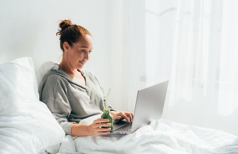 Woman using mobile phone while sitting on bed