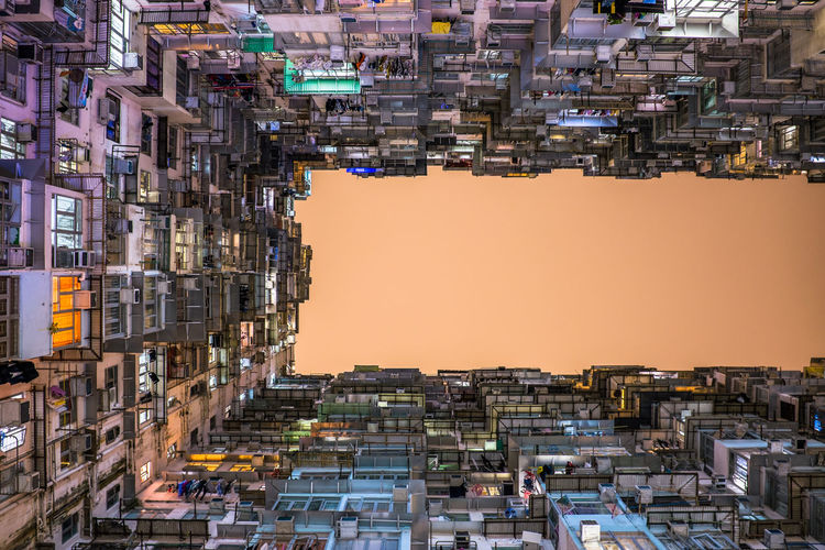 Directly below shot of buildings against clear sky during sunset