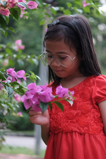 Flower Flowering Plant One Person Child Women Real People Girls Plant Females Leisure Activity Glasses Lifestyles Fragility Vulnerability  Childhood Focus On Foreground Freshness Day Pink Color Innocence Flower Head Hairstyle Outdoors