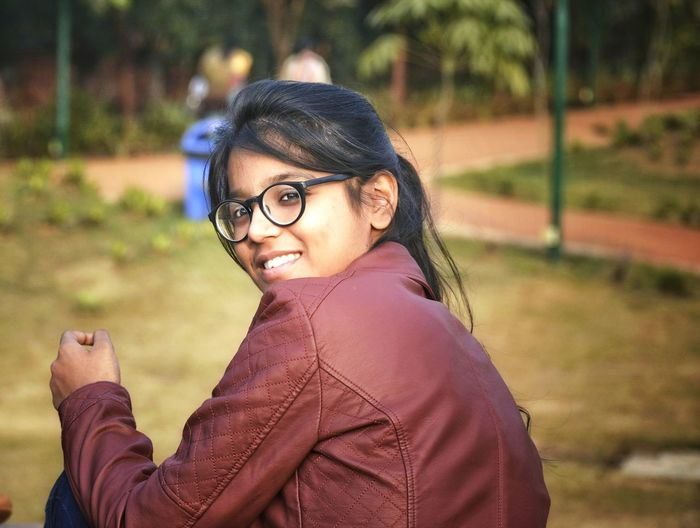 Side view portrait of smiling girl wearing jacket sitting in public park