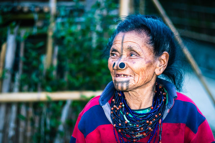 Apatani tribal women facial expression with her traditional nose lobes and blurred background