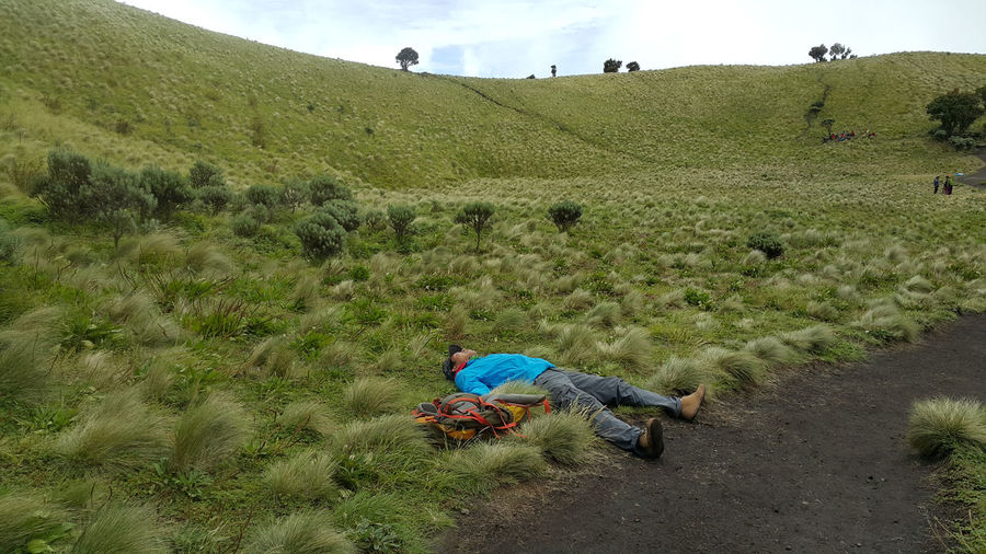 Hiker laying down on field