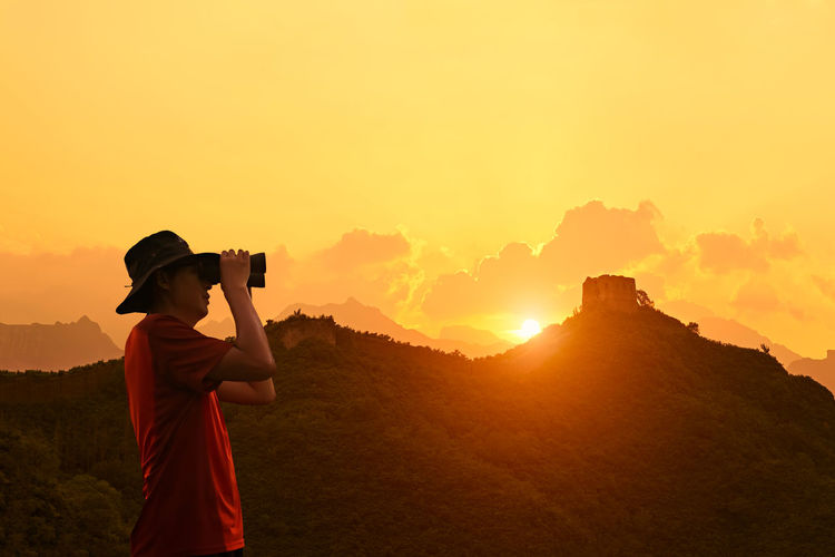 Side view of man looking through binoculars against great wall of china during sunset