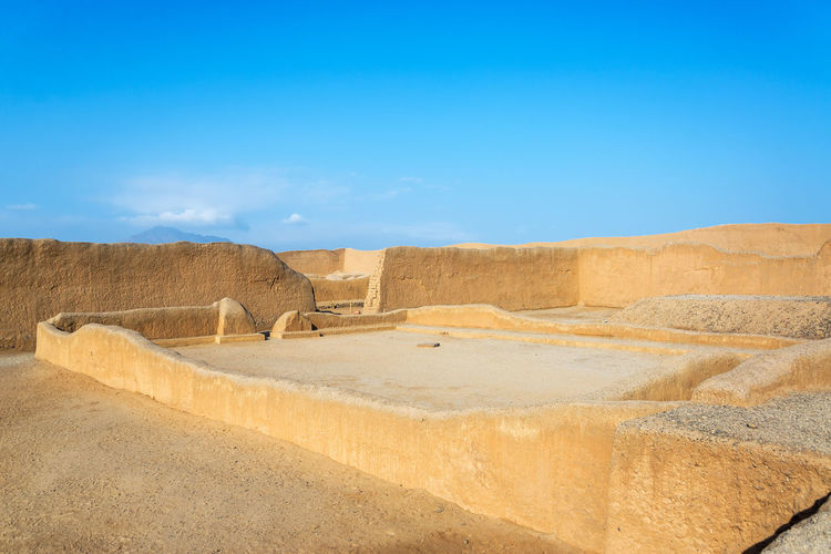 Pathway amidst adobe walls of ancient city against clear blue sky
