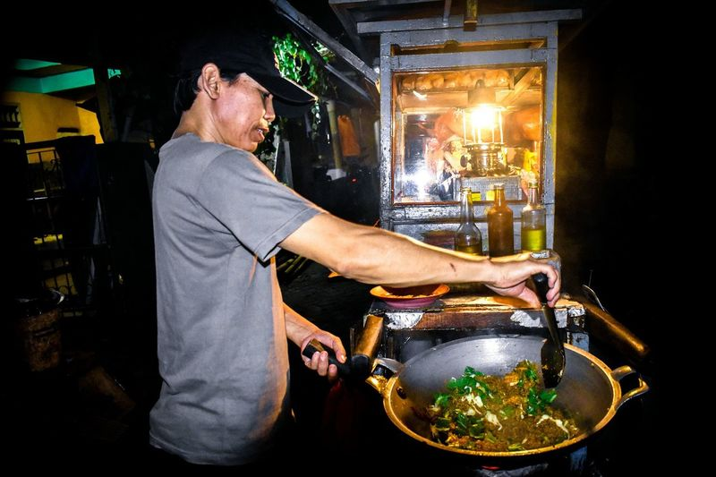 Side view of chef preparing food at market stall during night
