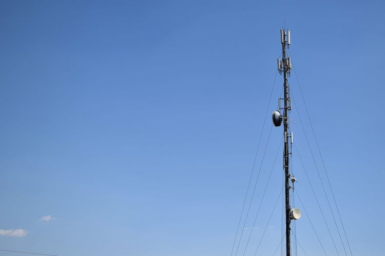 Low angle view of repeater tower against blue sky